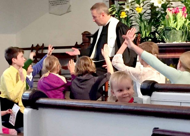 Kids raise their hand during a participatory children's time at the First Congregational Church of Stockbridge