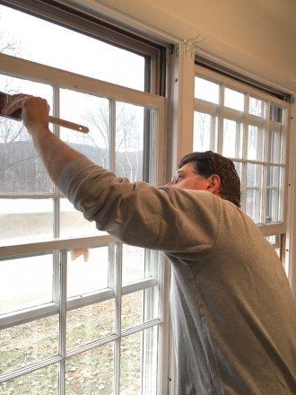 A man paints window trim.