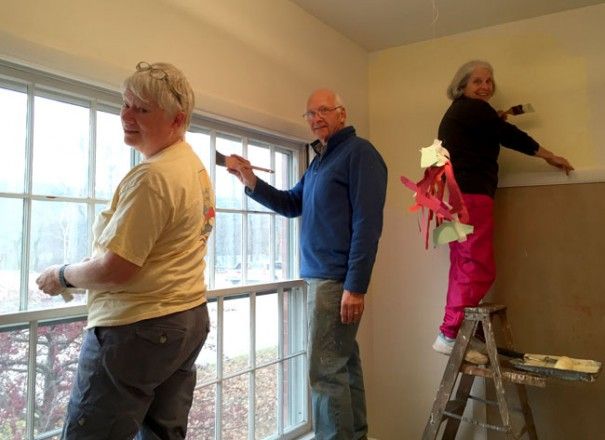 A man and two women apply a fresh coat of paint to the nursery