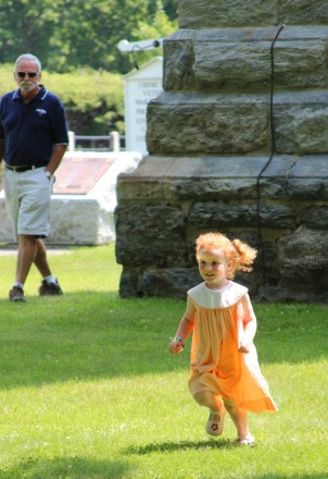 a cute young girl in an orange dress dances in the sun in front of the church