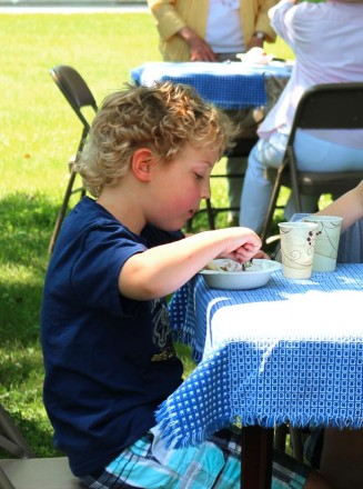 a cute young boy devours his strawberries and shortcake in front of the church