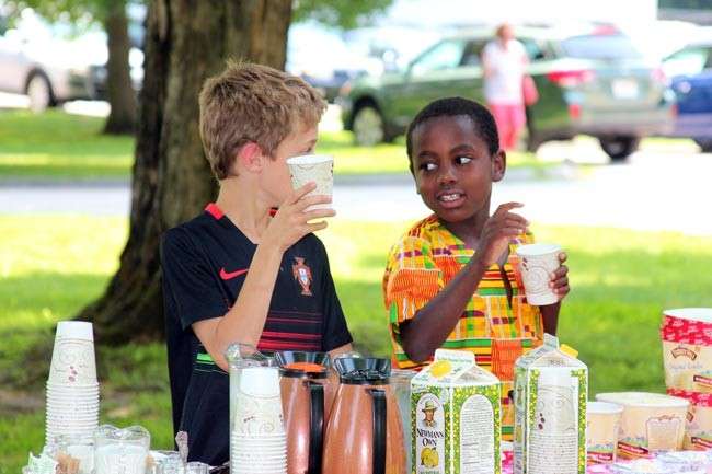 two young boys drink lemonade