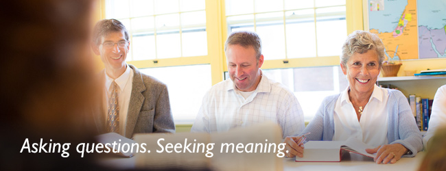 Asking questions. Seeking meaning. A group of people gather around a table in Bible study.