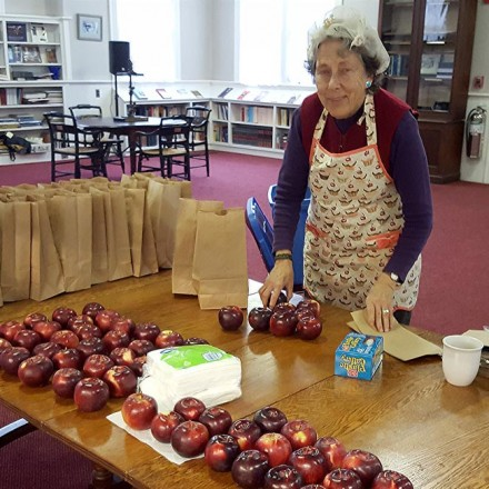 A woman stands over bags of prepared foods and fresh apples