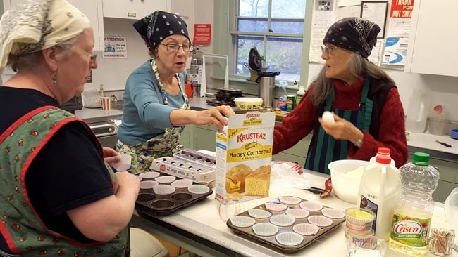 Three women bake cornbread for Cathedral in the Night