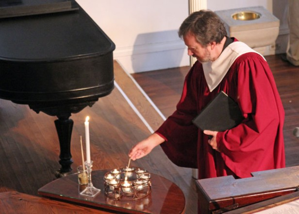 A man lights candles to remember a loved one on All Saints Day